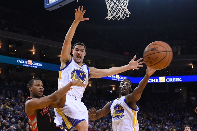 January 2, 2015; Oakland, CA, USA; Toronto Raptors guard Kyle Lowry (7) passes the basketball against Golden State Warriors guard Klay Thompson (11) and forward Harrison Barnes (40) during the second quarter at Oracle Arena. Mandatory Credit: Kyle Terada-USA TODAY Sports