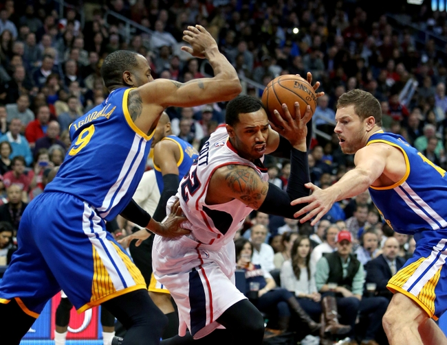 Feb 6, 2015; Atlanta, GA, USA; Atlanta Hawks forward Mike Scott (32) drives against Golden State Warriors guard Andre Iguodala (9) and forward David Lee (10) in the fourth quarter of their game at Philips Arena. The Hawks won 124-116. Scott was fouled by Lee on the play. Mandatory Credit: Jason Getz-USA TODAY Sports