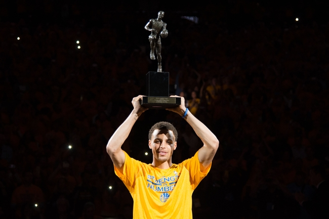 May 5, 2015; Oakland, CA, USA; Golden State Warriors guard Stephen Curry (30) hoists the MVP trophy before game two of the second round of the NBA Playoffs against the Memphis Grizzlies at Oracle Arena. Mandatory Credit: Kyle Terada-USA TODAY Sports