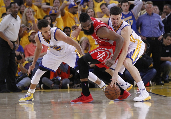May 21, 2015; Oakland, CA, USA; Houston Rockets guard James Harden (13) turns the ball over against the defense of Golden State Warriors guard Stephen Curry (30) and guard Klay Thompson (11) during the second half in game two of the Western Conference Finals of the NBA Playoffs. at Oracle Arena. Mandatory Credit: Cary Edmondson-USA TODAY Sports