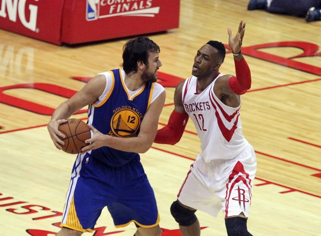 May 23, 2015; Houston, TX, USA; Golden State Warriors center Andrew Bogut (12) looks to drive as Houston Rockets center Dwight Howard (12) defends during the game in game three of the Western Conference Finals of the NBA Playoffs at Toyota Center. Mandatory Credit: Thomas B. Shea-USA TODAY Sports