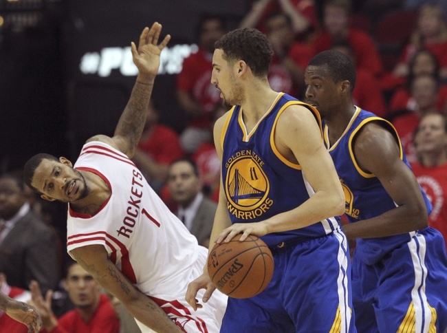 May 25, 2015; Houston, TX, USA; Golden State Warriors guard Klay Thompson (11) dribbles as Houston Rockets forward Trevor Ariza (1) defends during the second half in game four of the Western Conference Finals of the NBA Playoffs. at Toyota Center. Mandatory Credit: Thomas B. Shea-USA TODAY Sports