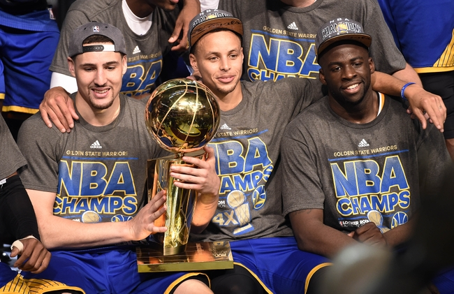 Jun 16, 2015; Cleveland, OH, USA; Golden State Warriors guard Klay Thompson (11), guard Stephen Curry (30) and Golden State Warriors forward Draymond Green (23) celebrates with the Larry O'Brien Trophy after beating the Cleveland Cavaliers in game six of the NBA Finals at Quicken Loans Arena. Mandatory Credit: Bob Donnan-USA TODAY Sports