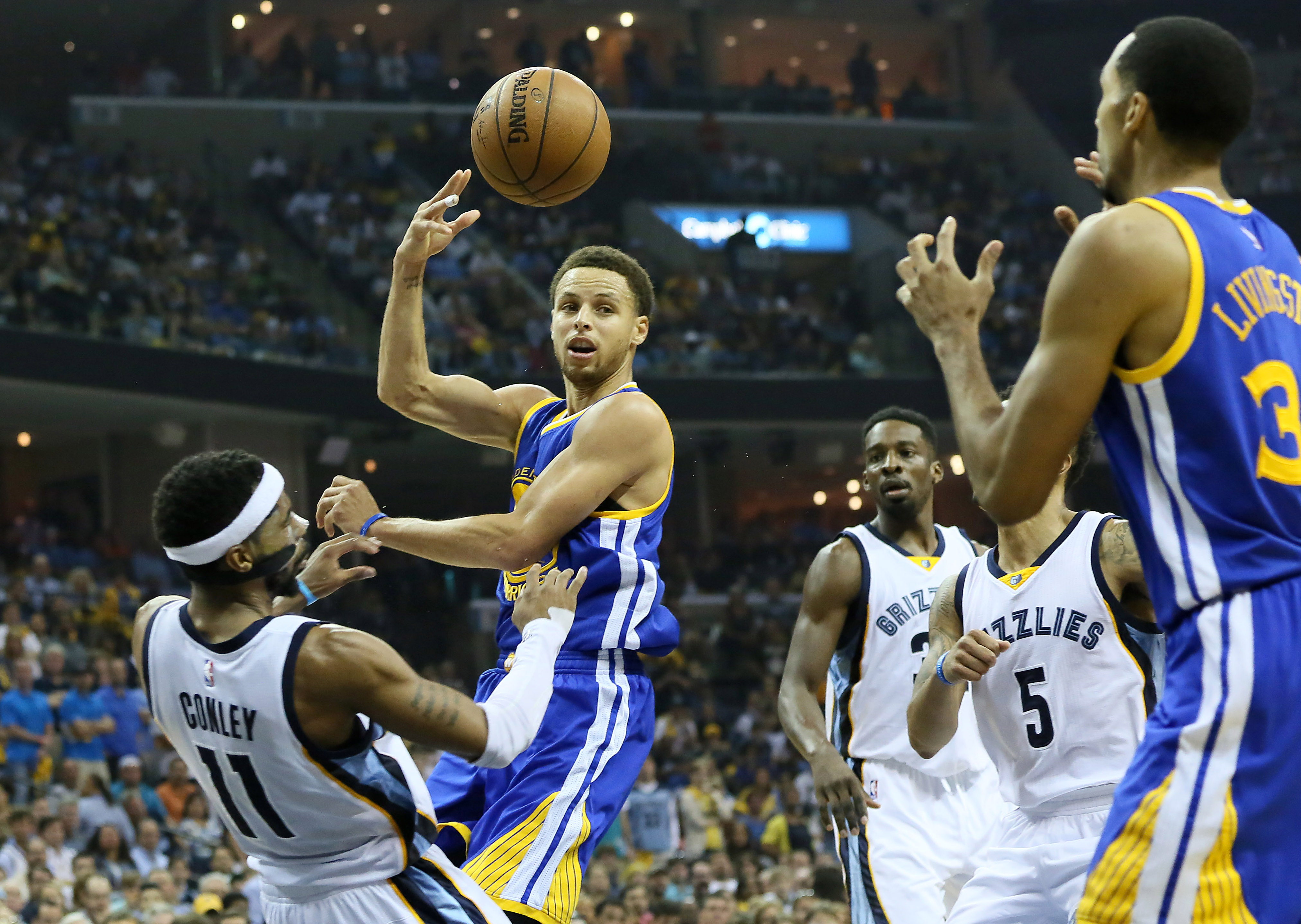 May 15, 2015; Memphis, TN, USA; Golden State Warriors guard Stephen Curry (30) passes to guard Shaun Livingston (34) as Memphis Grizzlies guard Mike Conley (11) defends in the third quarter of game six of the second round of the NBA Playoffs at FedExForum. Mandatory Credit: Nelson Chenault-USA TODAY Sports