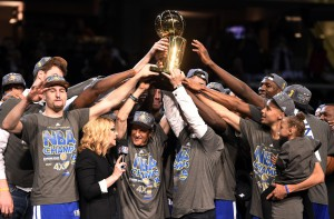 Jun 16, 2015; Cleveland, OH, USA; The Golden State Warriors celebrate with the Larry O'Brien Trophy after beating the Cleveland Cavaliers in game six of the NBA Finals at Quicken Loans Arena. Mandatory Credit: Bob Donnan-USA TODAY Sports
