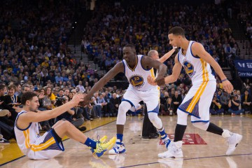January 11, 2016; Oakland, CA, USA; Golden State Warriors guard Klay Thompson (11, left) is helped up by forward Draymond Green (23) and guard Stephen Curry (30) during the fourth quarter against the Miami Heat at Oracle Arena. The Warriors defeated the Heat 111-103. Mandatory Credit: Kyle Terada-USA TODAY Sports