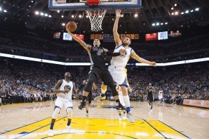 April 7, 2016; Oakland, CA, USA; San Antonio Spurs guard Danny Green (14) shoots the basketball against Golden State Warriors center Andrew Bogut (12) during the third quarter at Oracle Arena. The Warriors defeated the Spurs 112-101. Mandatory Credit: Kyle Terada-USA TODAY Sports