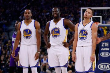 Andre Iguodala, Draymond Green, and Stephen Curry standing on court